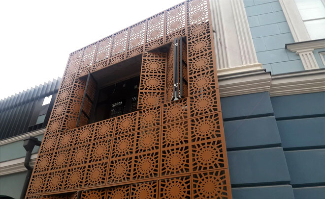 Facade cladding with perforated tiles